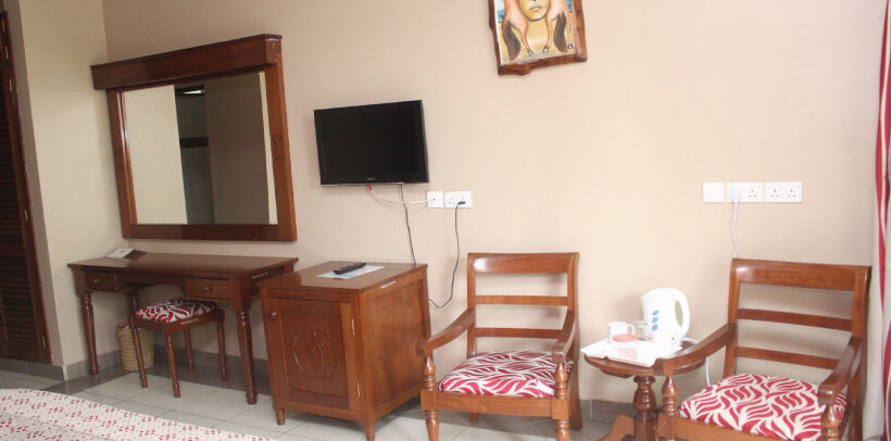 Image showing a chair, wall mounted TV, Electric Kettle, Mini-cupboard/desk and a wall hanging all in a room in the Mombasa Sports Club Accommodation Wing.